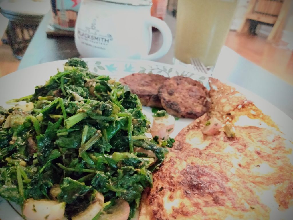 "Sauteed greens with fresh eggs and vegetarian ""sausage"" patties"