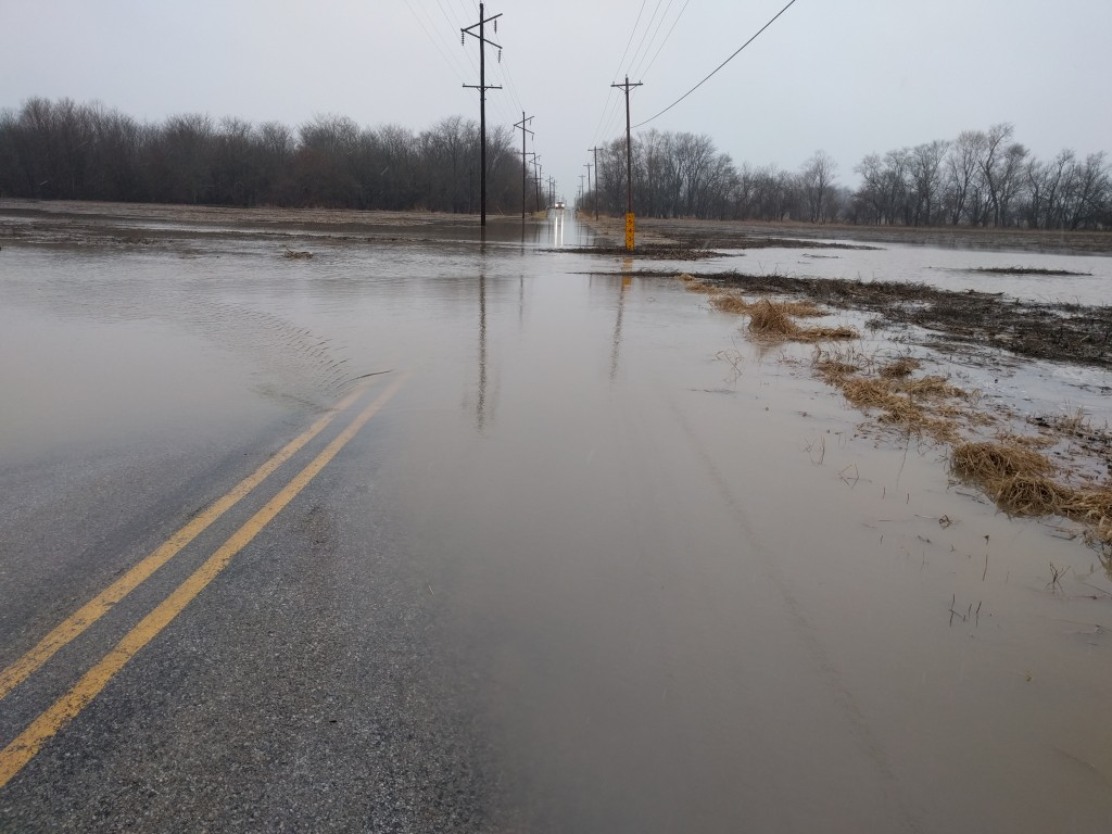 A creek overflows, creating flooded corn fields and road floods